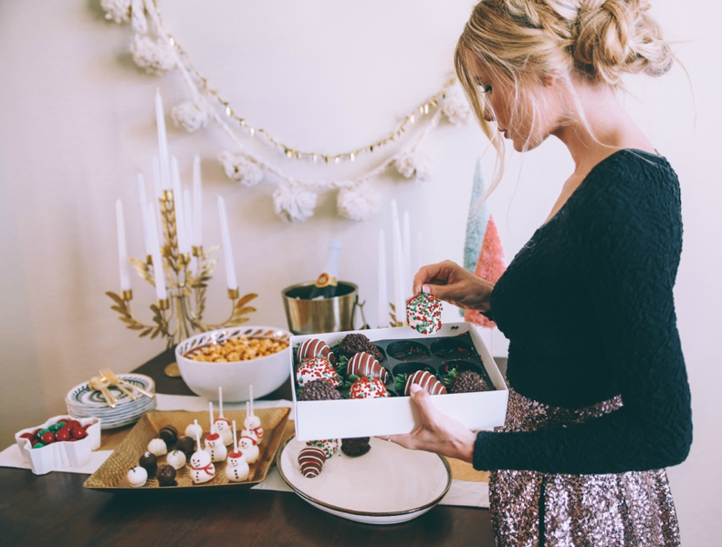 Woman Setting Out Chocolate-Covered Strawberries