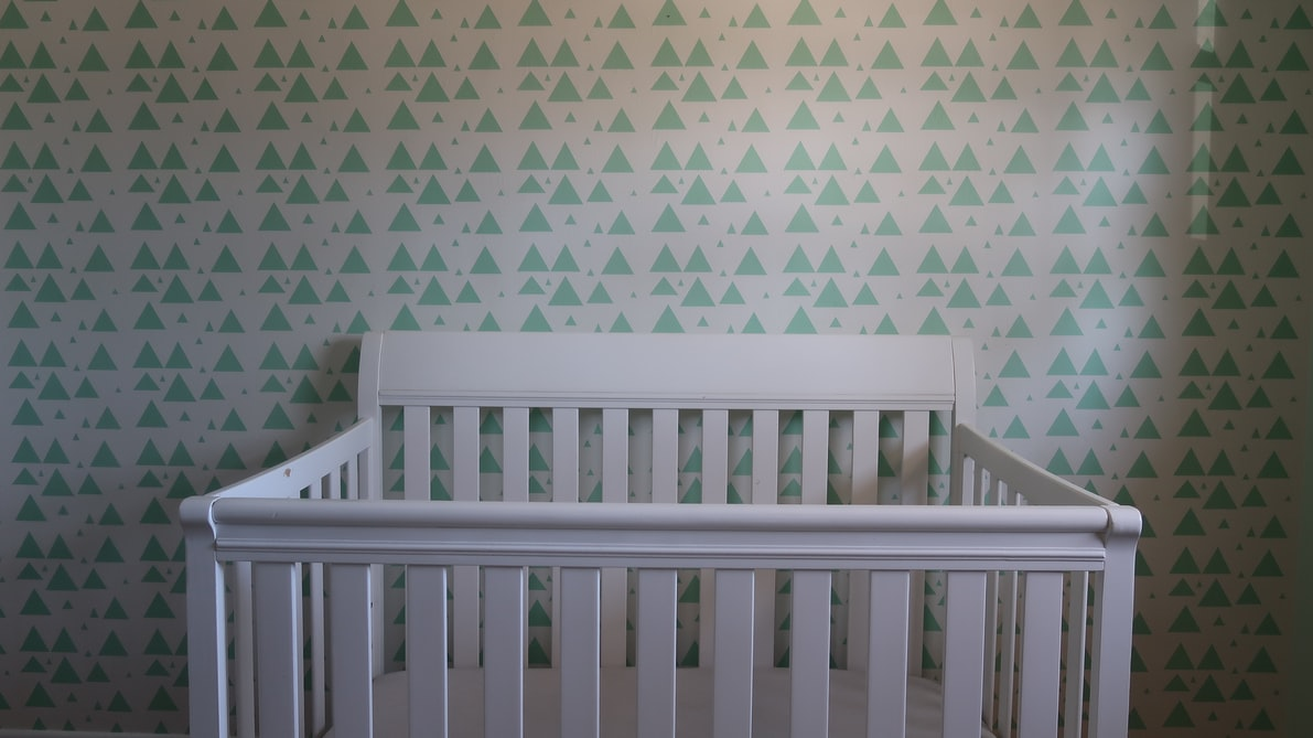 White Crib in a Nursery with Patterned Wallpaper